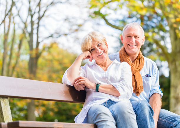 A happy couple sits on a bench outdoors.
